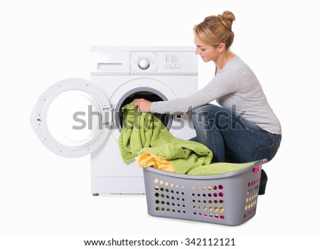 Young woman loading washing machine over white background - stock photo