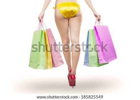 Young woman long legs in high heels holding shopping bags. isolated on white