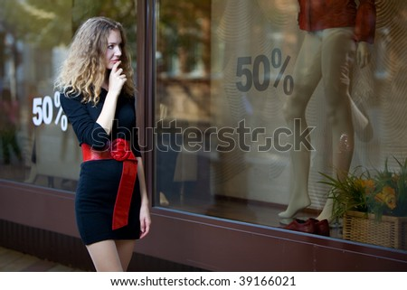 young woman look in shop windows with sale - stock photo