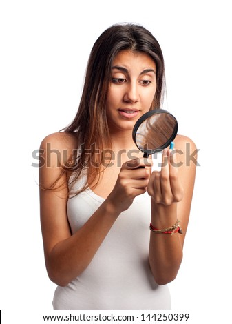 young woman looking a pill through magnifying glass isolated on white background