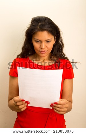 young woman looking alarmed at a document - stock photo