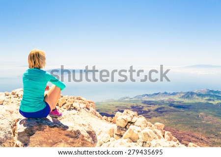 Young woman looking and meditation outside natural beautiful inspirational landscape environment, fitness and exercising motivation and inspiration in sunny mountains over blue sky and ocean sea. - stock photo
