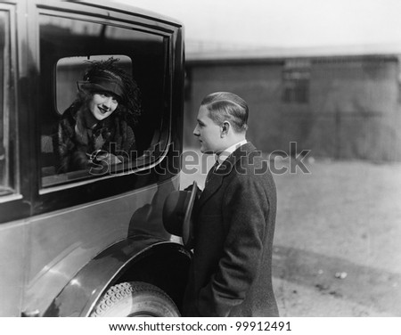 Young woman looking at a man through a car window - stock photo