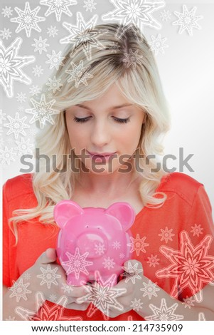Young woman looking at a piggy bank held by her hands against snowflakes on silver - stock photo