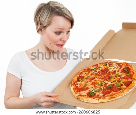 Young woman looking at a pizza and drooling over, isolated on white - stock photo
