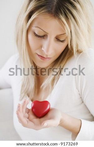 young woman looking at a red love heart