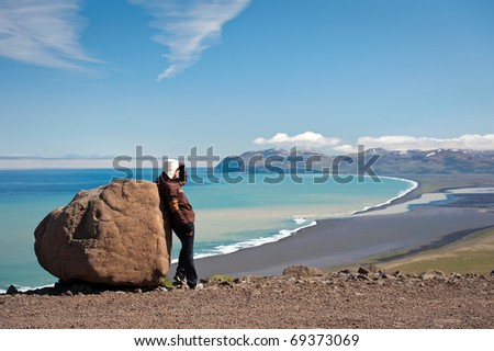 young woman looking at amazing Icelandic landscape - stock photo
