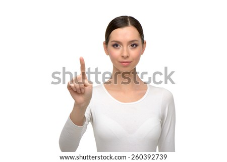 Young woman looking at camera and pointing at something. Isolated on white background - stock photo