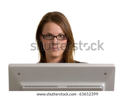 young woman looking at camera over the top of desktop computer monitor