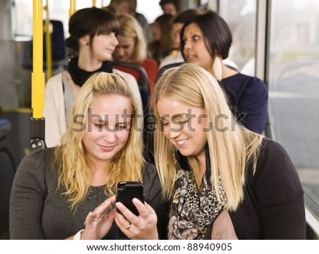 Young woman looking at cellphone while going by the bus - stock photo