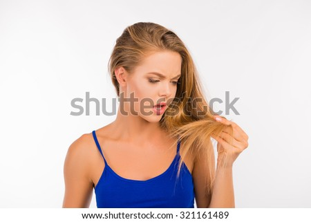 Young woman looking at damaged split ends - stock photo
