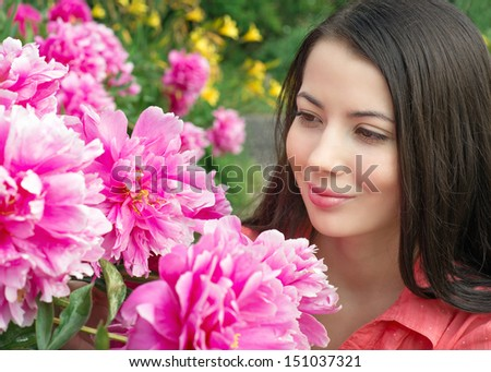 Young woman looking at flowers peonies