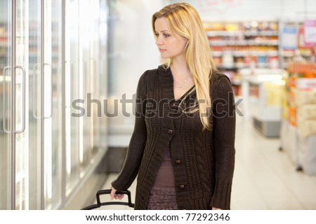 Young woman looking at goods in refrigerator section of supermarket - stock photo