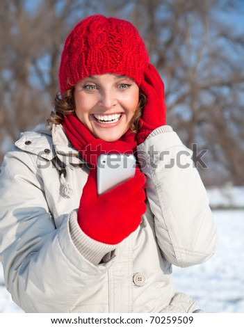 Young woman looking at her phone and looking surprised - stock photo