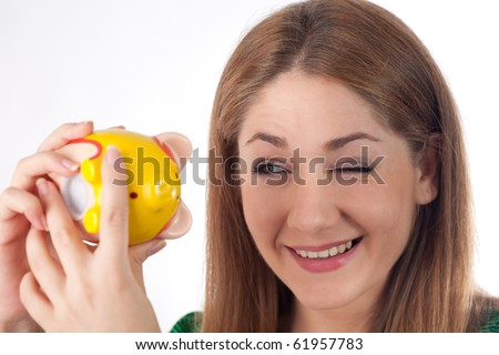 young woman looking at her piggybank - stock photo