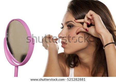 young woman looking at her wrinkles in front of the mirror
