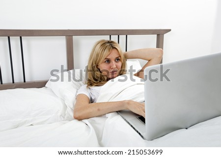 Young woman looking at laptop in bed