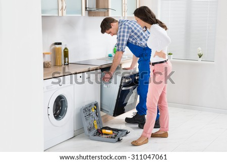 Young Woman Looking At Male Worker In Overall Repairing Oven In Kitchen