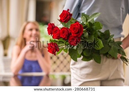 Young woman looking at man with flower bouquet behind the back. - stock photo