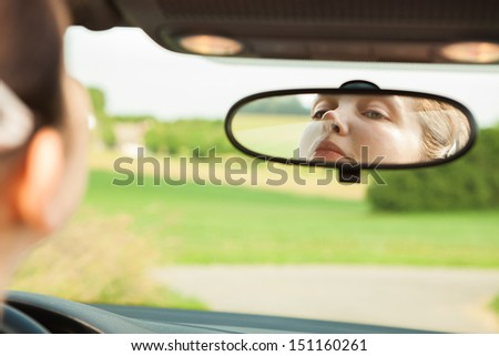 Young Woman Looking At Mirror While Driving The Car - stock photo
