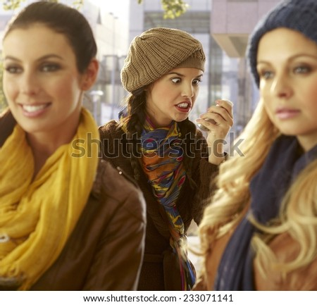 Young woman looking at mobile angry, friends waiting for her. - stock photo