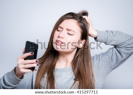 young woman looking at smart phone and remembers something, close-up isolation on gray - stock photo