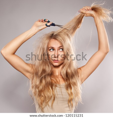 Young woman looking at split ends. Damaged long hair - stock photo