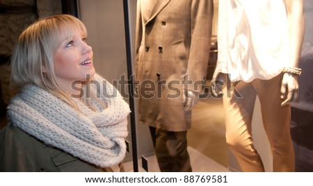 young woman looking at store window - stock photo