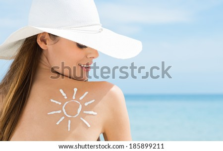 Young Woman Looking At Sun Drawn On Her Back With Suntan Lotion - stock photo