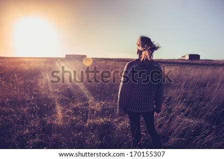 Young woman looking at sunset in field with her hair blowing