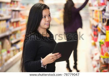 Young woman looking at the products while using digital tablet in shopping centre with person in the background - stock photo