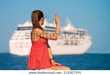 Young woman looking at the ship and waving her hand, view from the back - stock photo