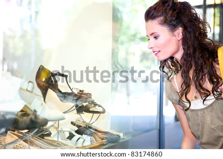 Young woman looking at the shop window - stock photo