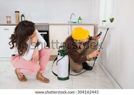 Young Woman Looking At Worker Spraying Insecticide Under The Windowsill In Kitchen - stock photo