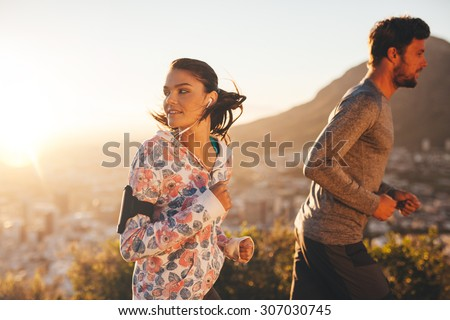 Young woman looking back while running with a man outdoors. Couple on morning run. - stock photo