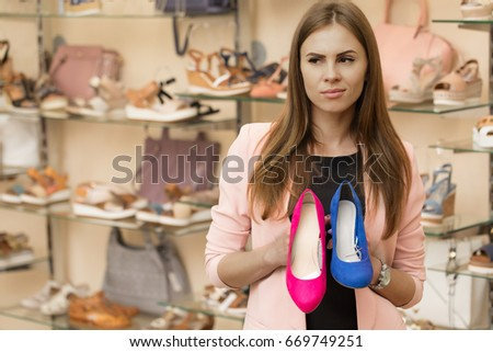 Young woman looking confused holding two high heel shoes posing at the store choosing choice deciding thinking doubting doubtful thoughtful consumerism glamour fashion retail concept