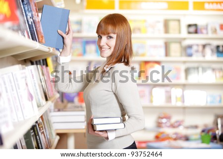 young woman looking for a book in a bookstore - stock photo