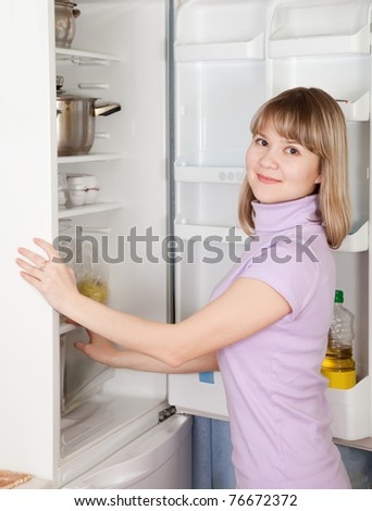 Young woman looking for something in the fridge at home