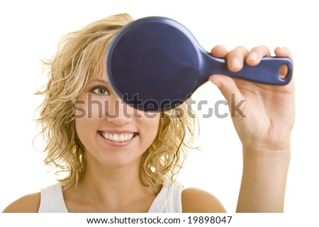 Young woman looking in a mirror - stock photo