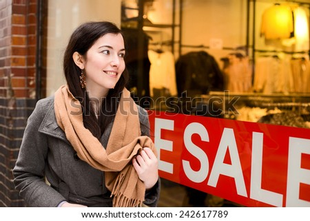 young woman looking in a shop window during the sales - stock photo