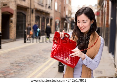 young woman looking in her handbag. - stock photo