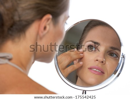 looking in mirror. young woman looking in mirror