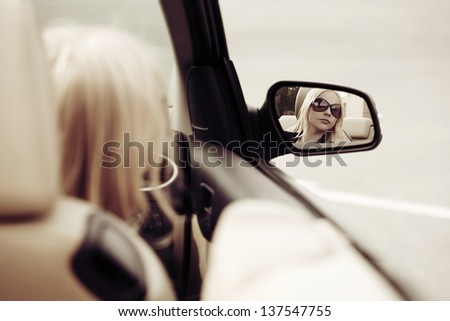 Young woman looking in the car mirror - stock photo