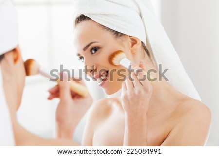 Young woman looking in the mirror and putting make-up on. Preparing for busy day.  - stock photo