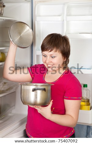 Young woman looking in to pan from  refrigerator