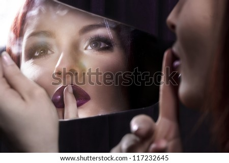 Young woman looking into a mirror - stock photo