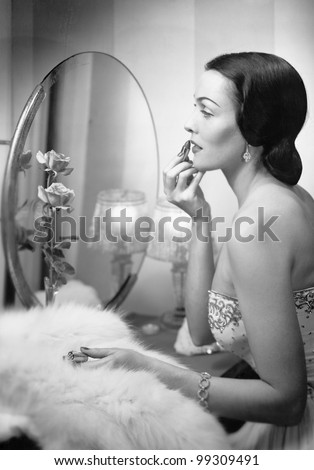 Young woman looking into a mirror and putting on make up - stock photo