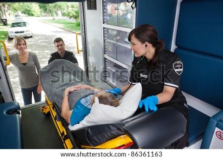 Young woman looking into ambulance at senior woman - stock photo