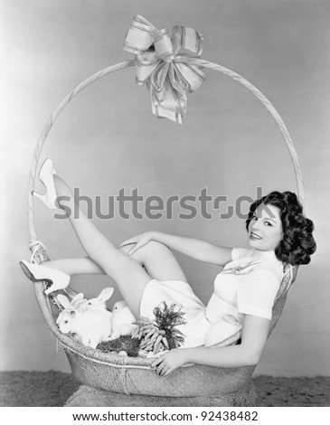 Young woman, looking like a present, sitting in gift basket with bunnies - stock photo