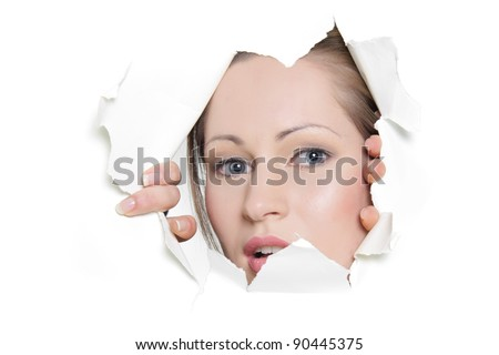 young woman looking out from hole in paper